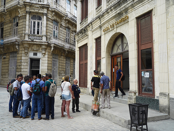 Locals and visitors to Cuba wait in front of a bank to exchange money or use credit cards to access cash – U.S. cards still not accepted.